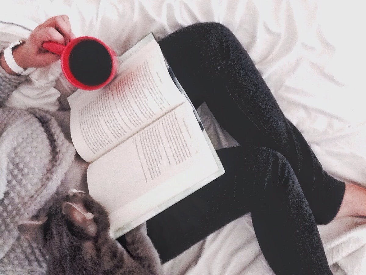 A woman reads in bed while holding coffee and snuggling her cat