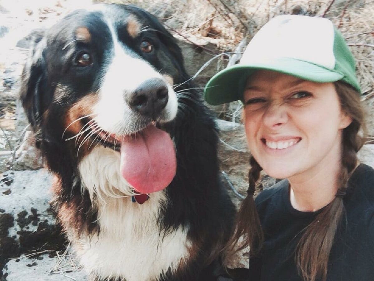 Girl takes a selfie with her Bernese Mountain Dog while out hiking