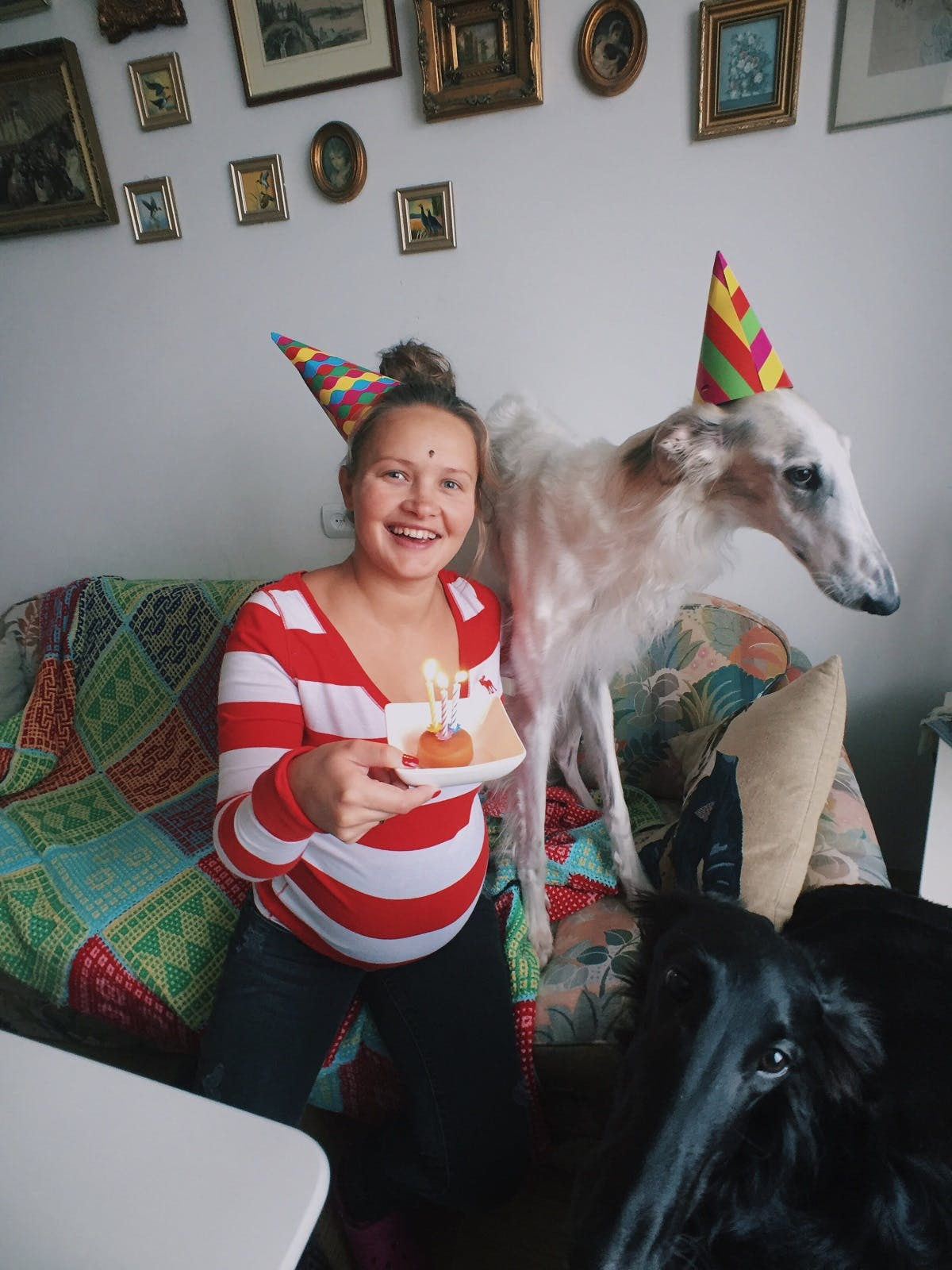 A girl and her dog wearing birthday hats on the couch