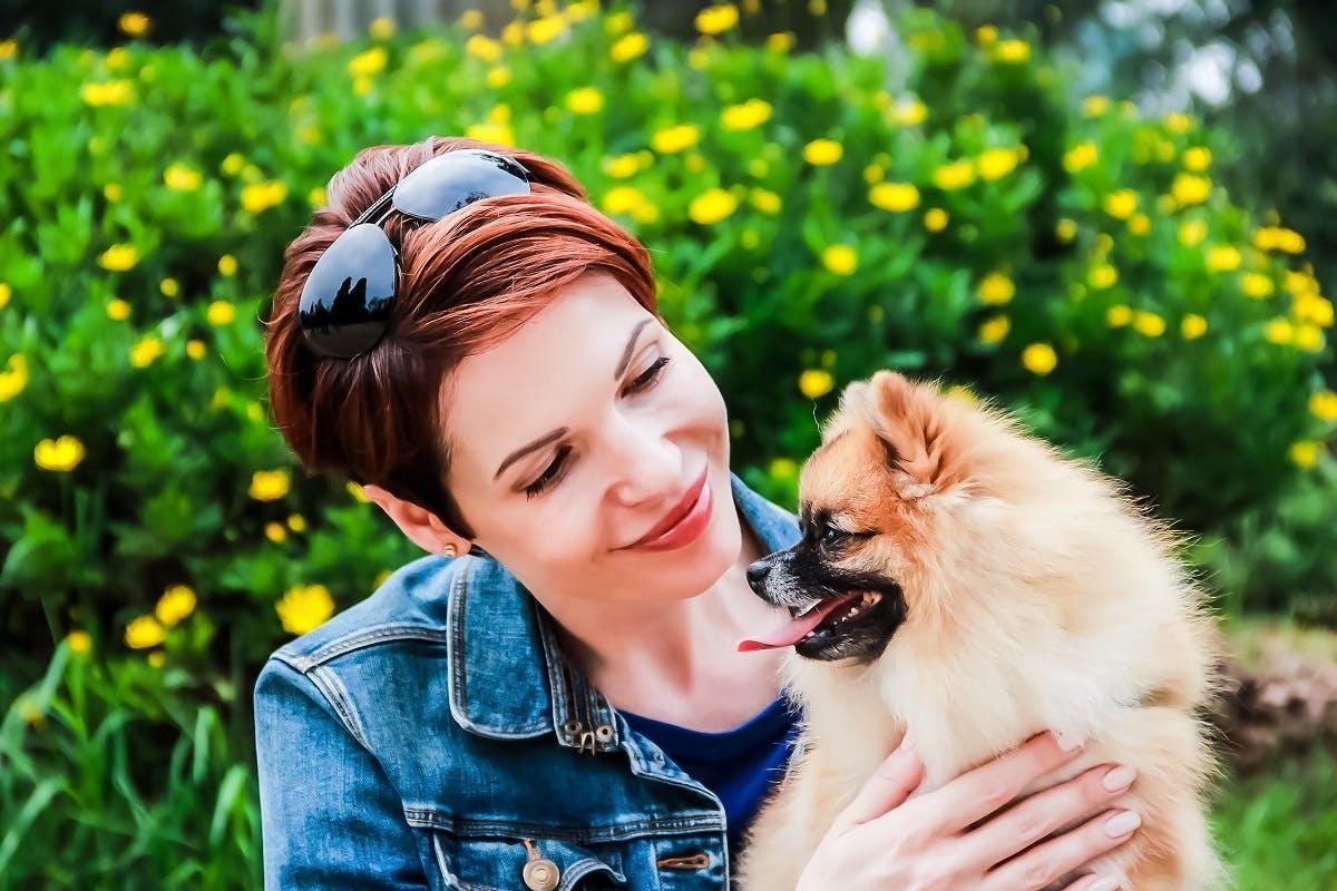 Girl smiles lovingly at her Pomeranian dog