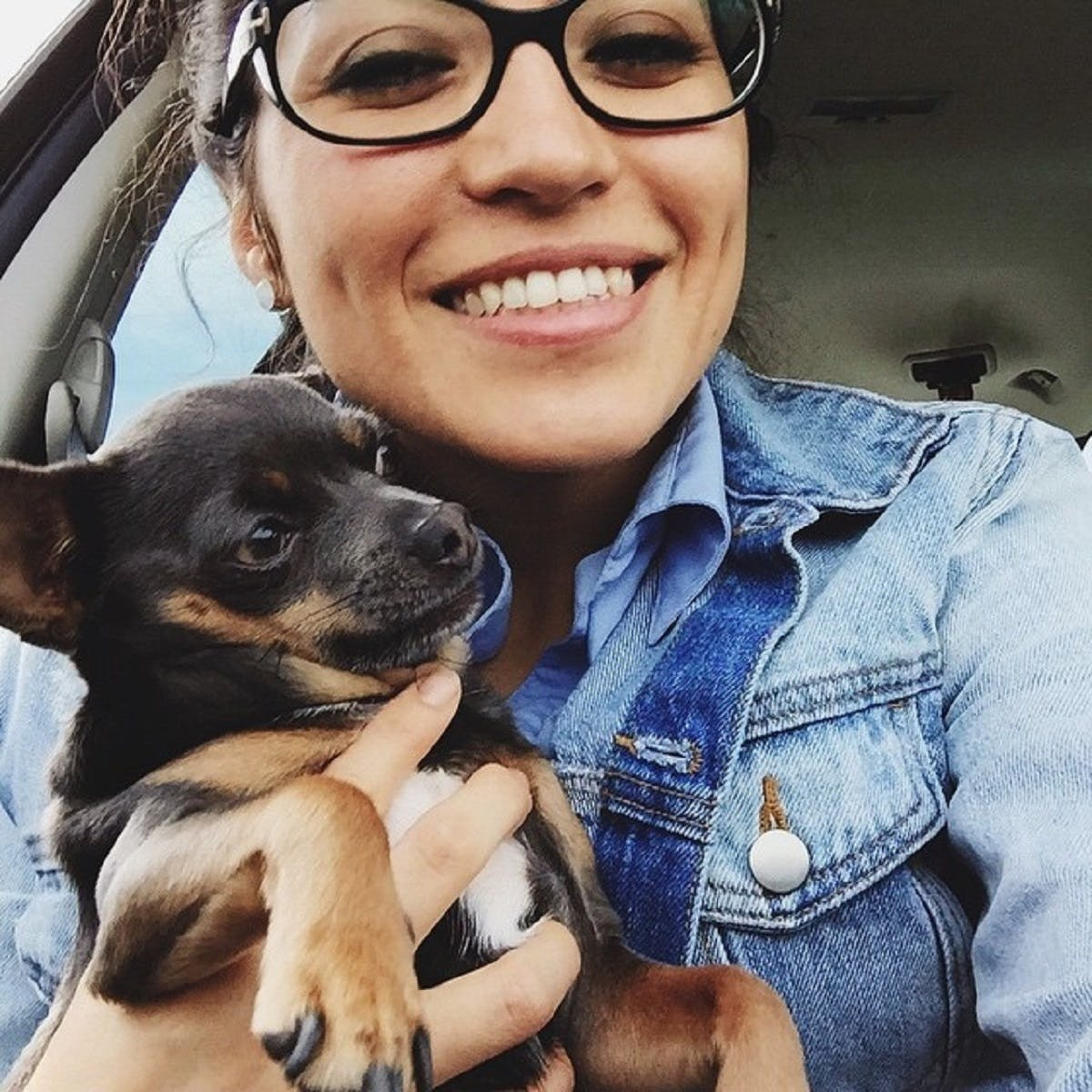 Woman takes a selfie with her dog in the car
