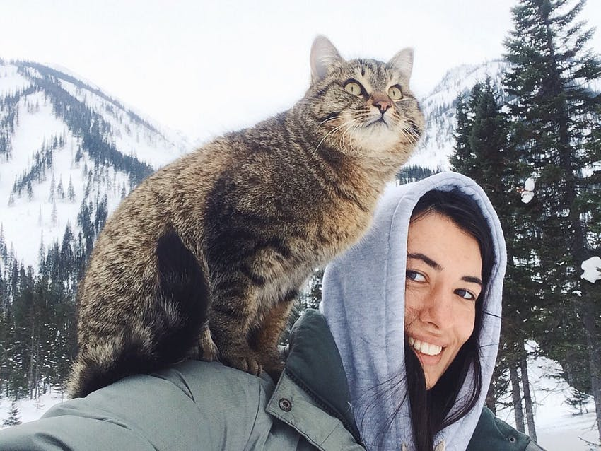 A fluffy cat sits on her smiling owners shoulder outside in the snow