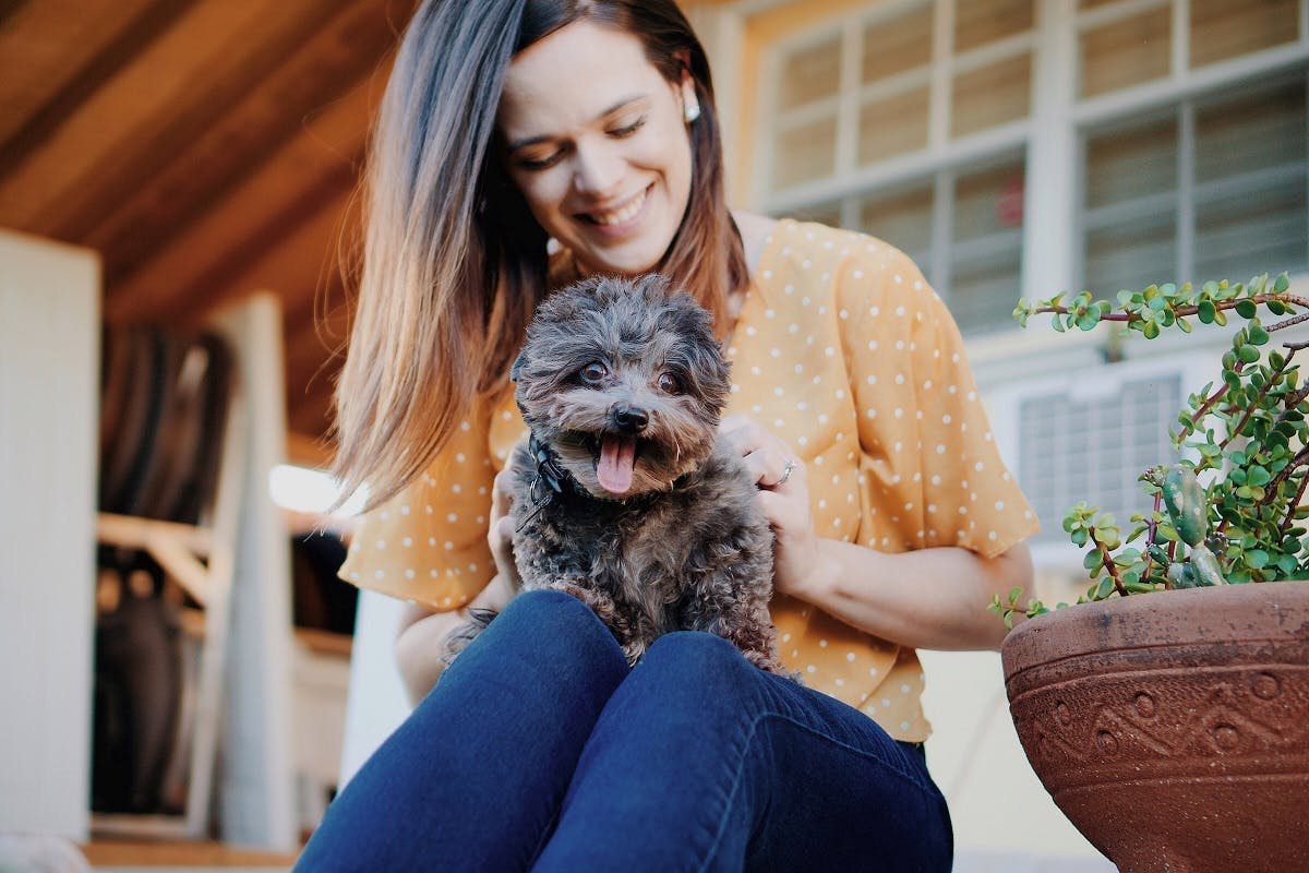 Woman sits on the porch with her dog in her lap