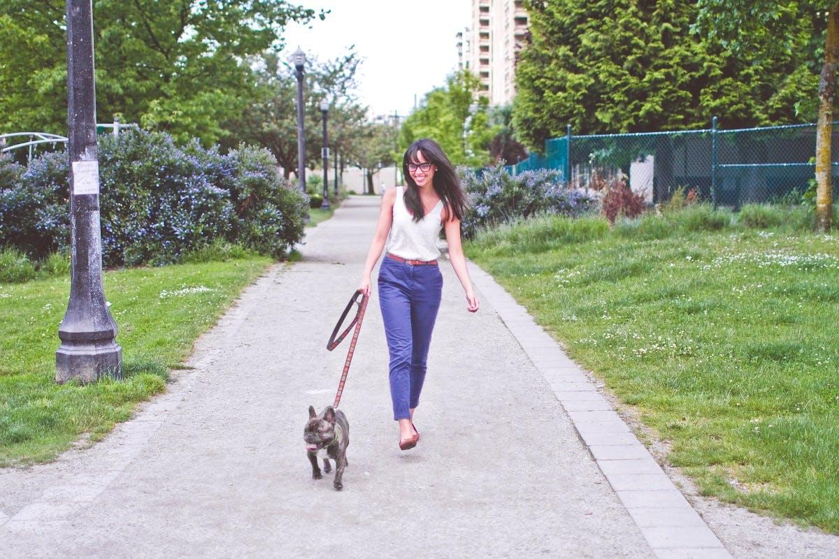 A woman with black hair walks her dog down a park sidewalk
